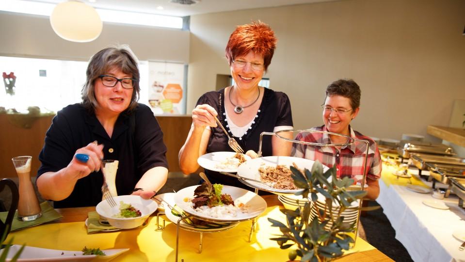 Foto: Drei Frauen bei Essensausgabe
