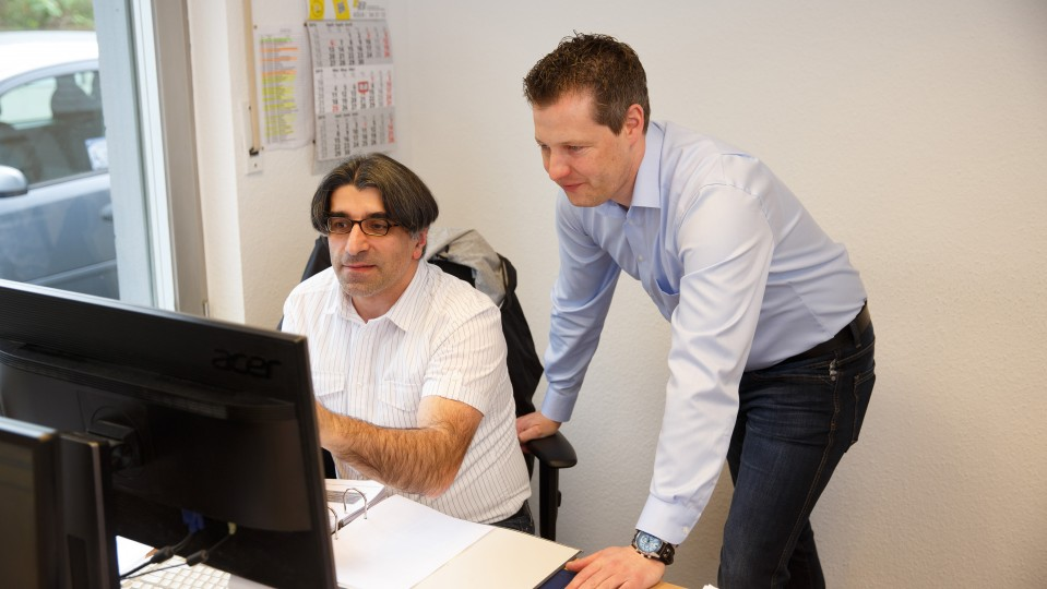 Foto: Ein Mann zeigt einem anderen Mann etwas auf seinem Computerbildschirm