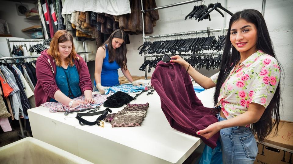 Foto: Mitarbeiterinnen beim Auszeichnen der Kleidung.