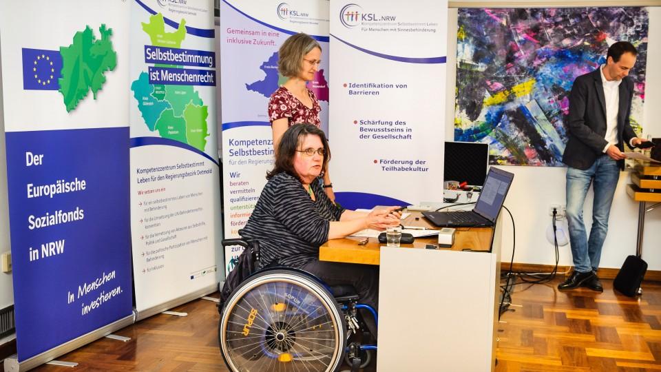 Foto: Zwei Frauen am Rednerpult. Eine Frau sitzt im Rollstuhl