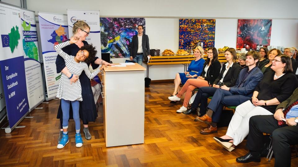 Foto: Eine Frau und ihre autistische Tochter stehen am Rednerpult