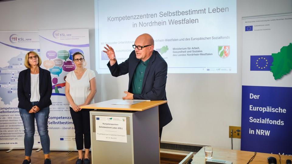 Foto: Mann am Rednerpult. Zwei Frauen stehen links