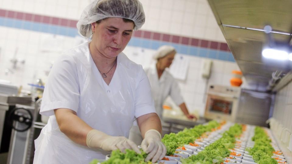 Foto zeigt Küchenhilfe beim Salat drapieren