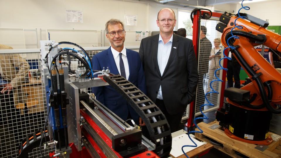 Foto: Zwei Menschen stehen neben einer Maschine