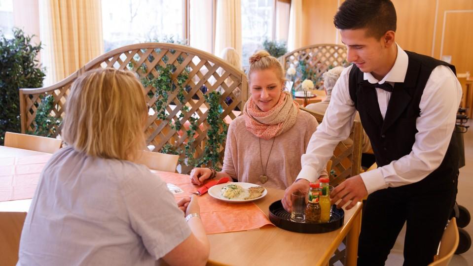 Foto: Junger Mann bedient zwei Frauen im Cafe