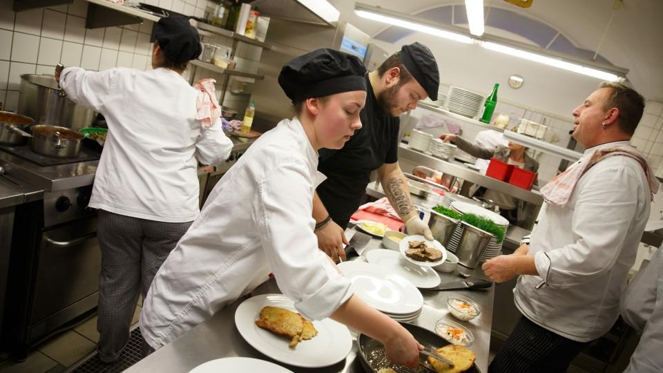 Foto: Junge Frau befüllt einen Teller in der Küche