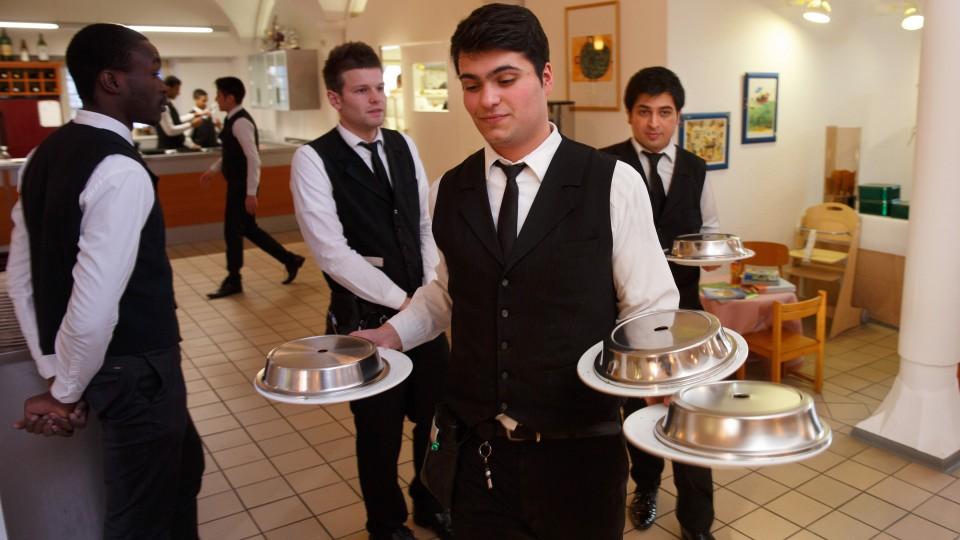 Foto: Junger Kellner mit drei Teller in der Hand