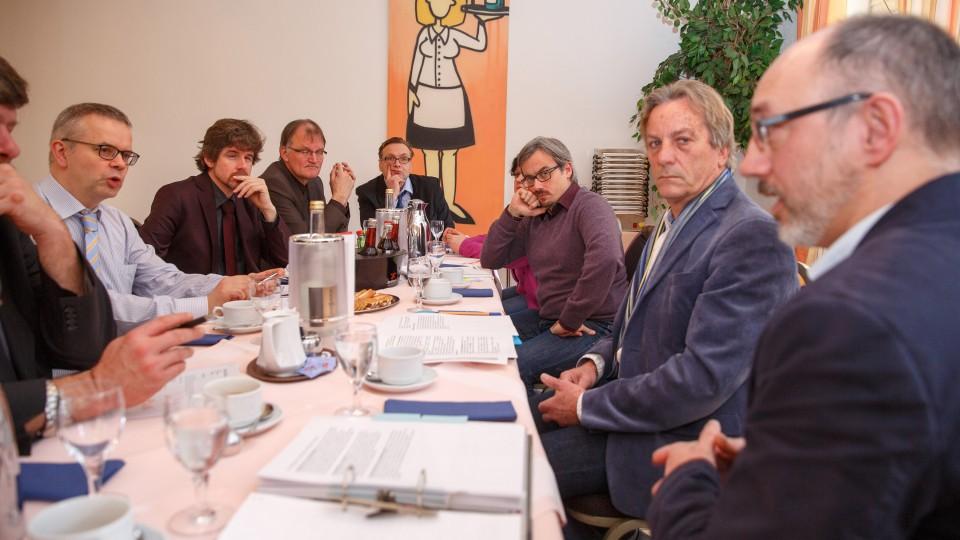 Foto: Acht Männer sitzen am Tisch und diskutieren