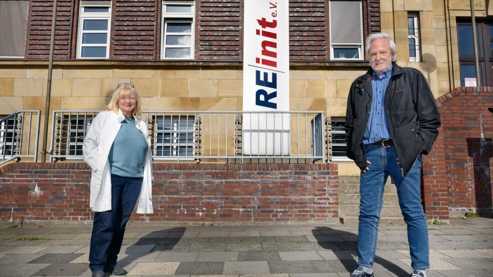Frau und Mann stehen vor einem Gebäude