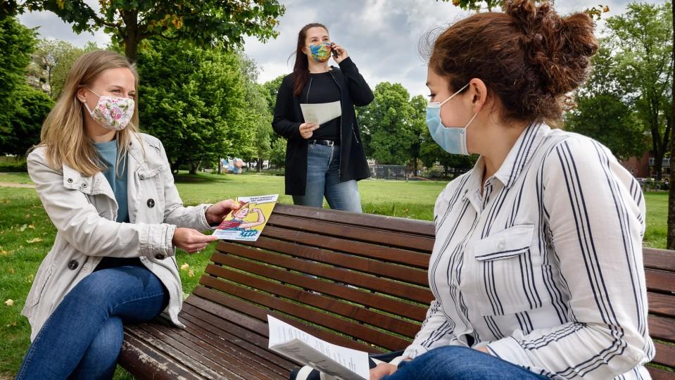 Drei junge Frauen mit Mundschutz-Masken abseits von anderen Menschen und unter Einhaltung des Mindestabstands im Park