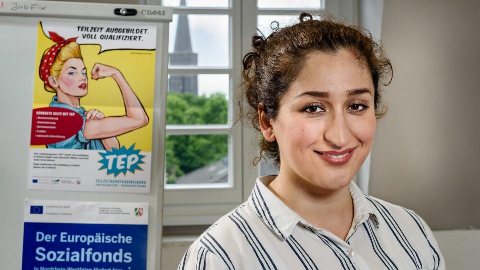 Eine junge Frau steht vor einem TEP-Plakat
