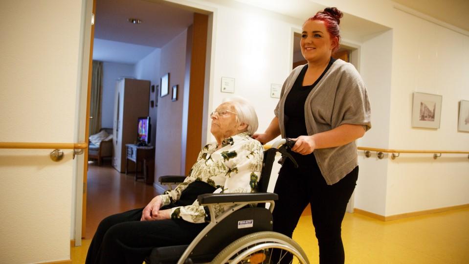 Foto: Junge Frau schiebt eine ältere Dame im Rollstuhl