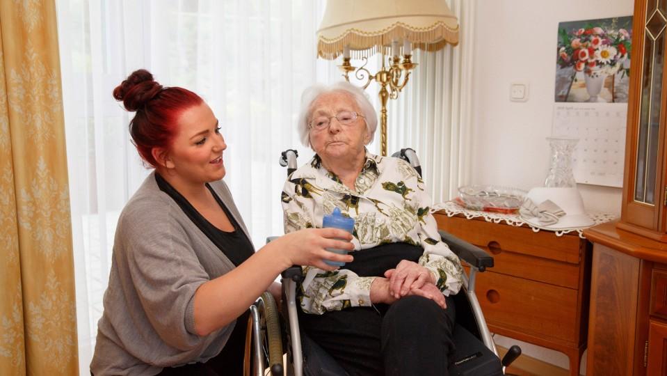 Foto: Junge Frau bietet einer älteren Damen, die im Rollstuhl sitzt, einen Becher zum Trinken