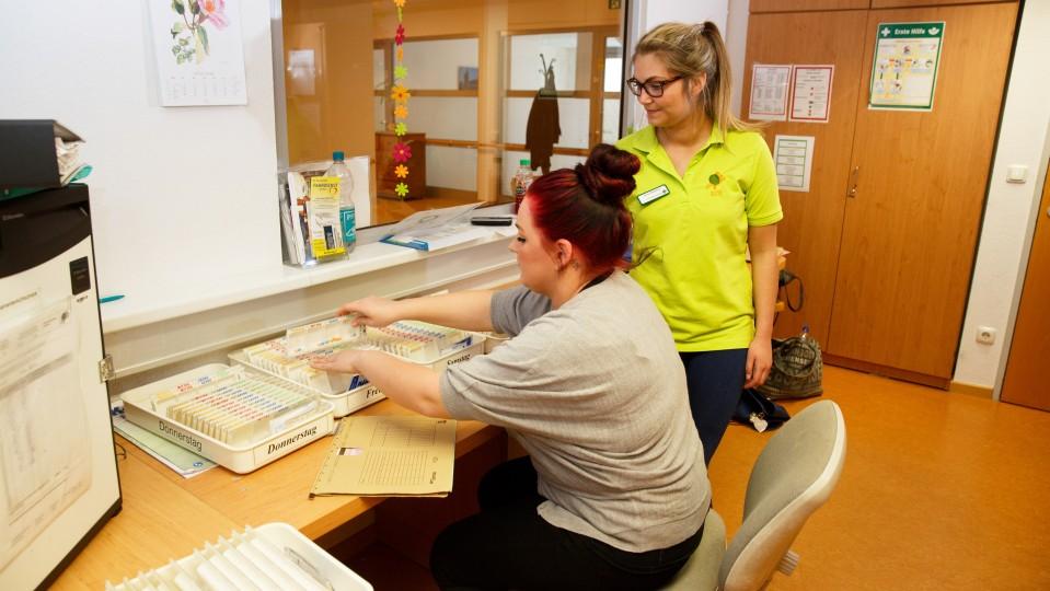 Foto: Zwei junge Frauen sortieren die Medikamentenschachteln