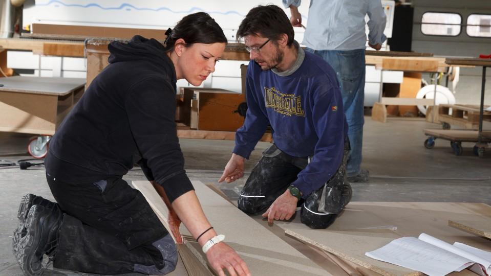 Foto: Eine Frau und ein Mann bei den Schreinereiarbeiten