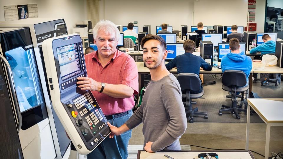 Foto: Kursleiter erklärt dem Auszubildenden Feinwerkmechaniker die Maschinenbedienung. Im Hintergrund lernen die anderen Kursteilnehmer das Programmieren von Maschinen.