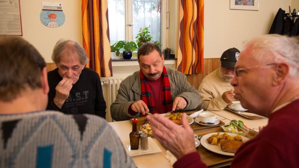 Foto: Fünf arbeitslose Männer bei gemeinsamen Mittagessen