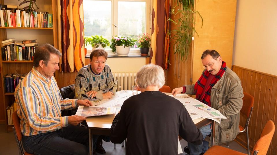 Foto: Vier Männer sitzen am Tisch und lesen Zeitungen