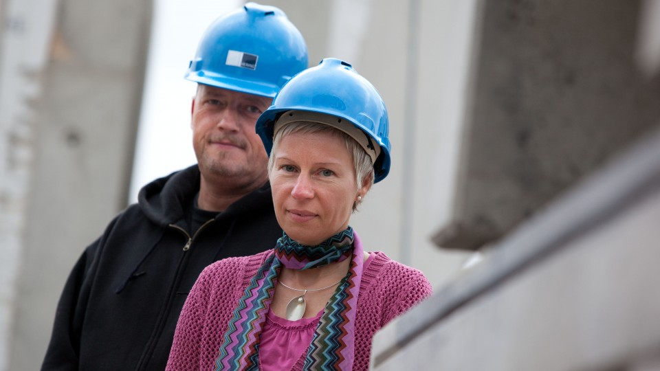 Mann und Frau mit Helm auf Baustelle