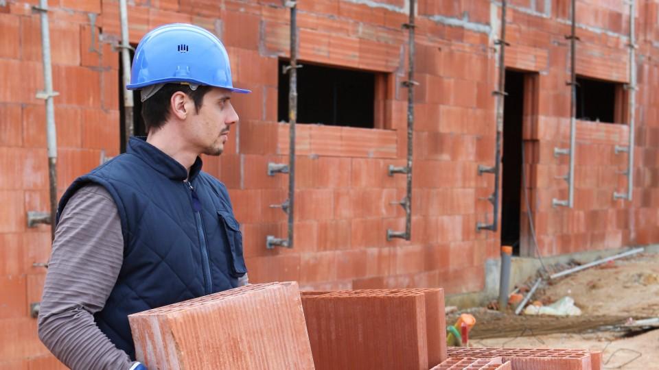 Mann mit Helm trägt Steine auf einer Baustelle