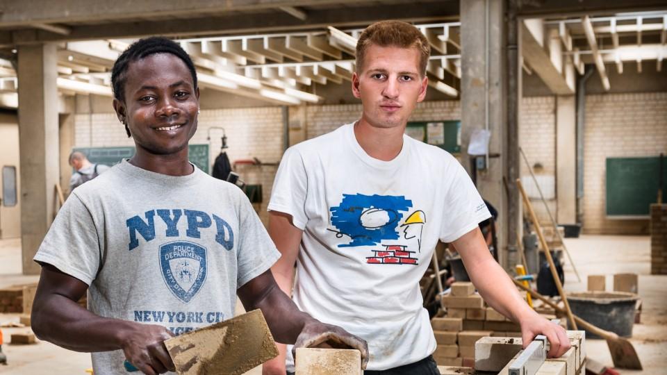 Junger Migrant mit Kollegen - Bauhandwerk Ausbildungszentrum