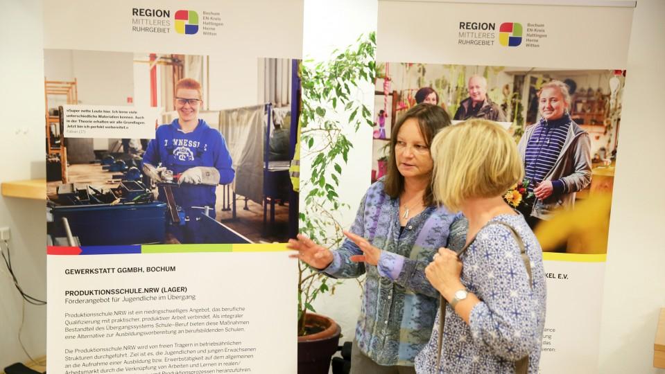 Foto: Zwei Frauen stehen vor einer Ausstellungstafel