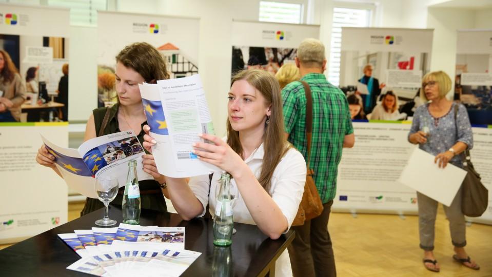 Foto: Zwei Frauen stehen am Tisch und schauen sich einen-Flyer an