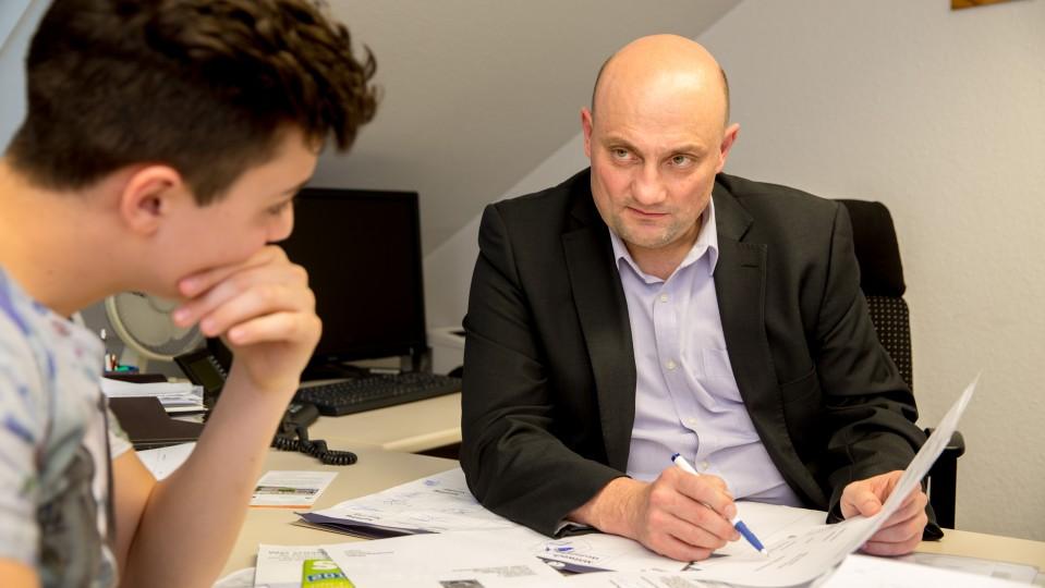 Berater erläutert Dokument, Jugendlicher hört aufmerksam zu