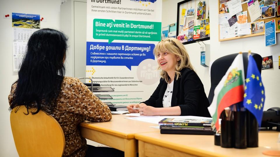 Zwei Frauen im Beratungsgespräch, im Hintergrund mehrsprachiges Plakat