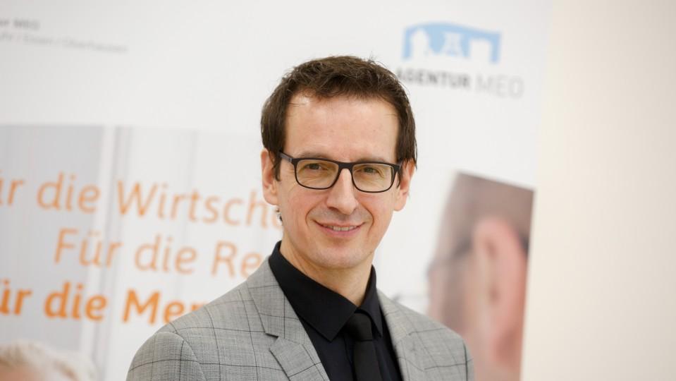 Bodo Kalveram, Leiter Regionalagentur MEO, Plaktawand mit Logo MEO im Hintergrund