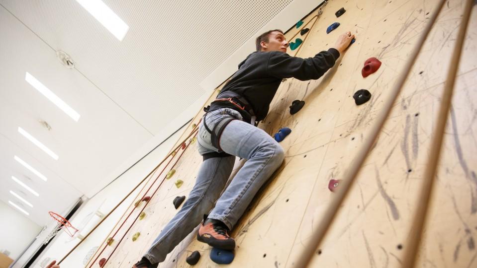 Foto: Junger Mann klettert die Wand hoch