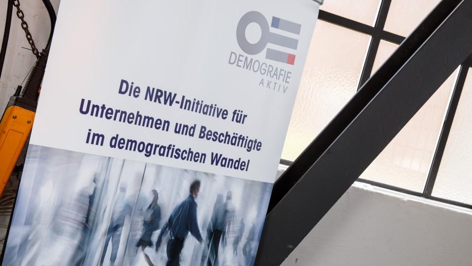 """Plakat zu Initiative """"Demografie aktiv"""" - Menschen in Drehtür gespiegelt"""