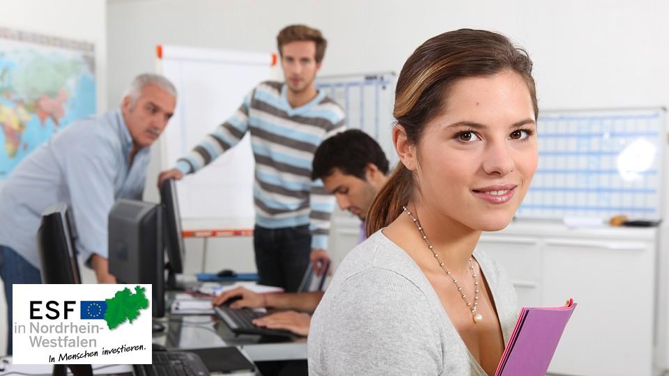 Foto: Junge Frau hält eine Mappe. Im Hintergrund befinden sich drei Männer
