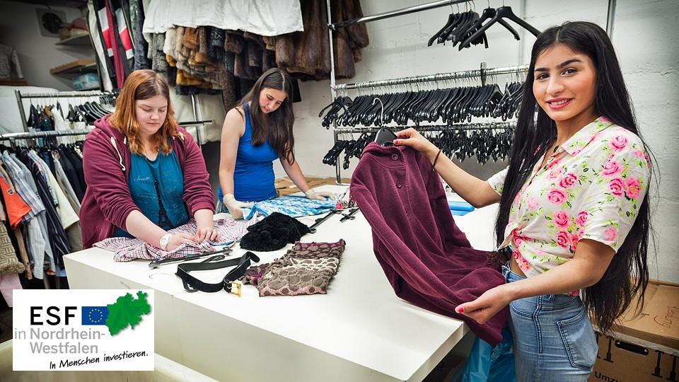 Foto: Mitarbeiterinnen beim Auszeichnen der Kleidung