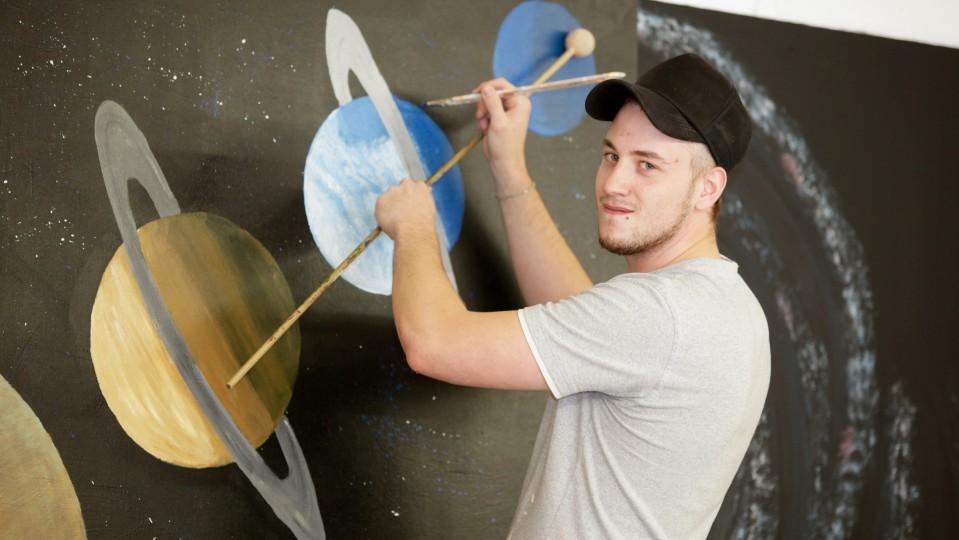 Foto: Junger Mann beim Ausmalen von Planetenbildern