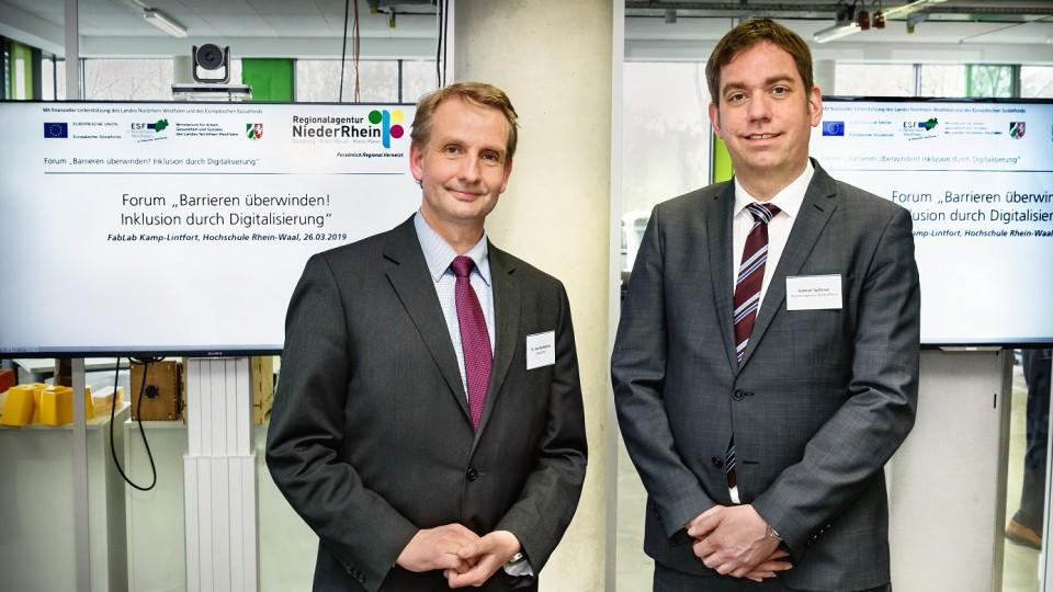 Vertreter des nordrhein-westfälischen Arbeitsministeriums(l.), Leiter der Regionalagntur, im Hintergrund Bildschirme mit Tagungstitel