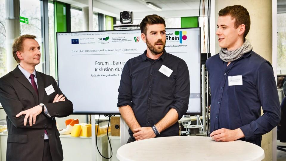Drei Männer stehen am Tisch. Ein junger Mann (r.) berichtet von seiner Ausbildung bei einem Dienstleister im Bereich der Digital- und Printmedien