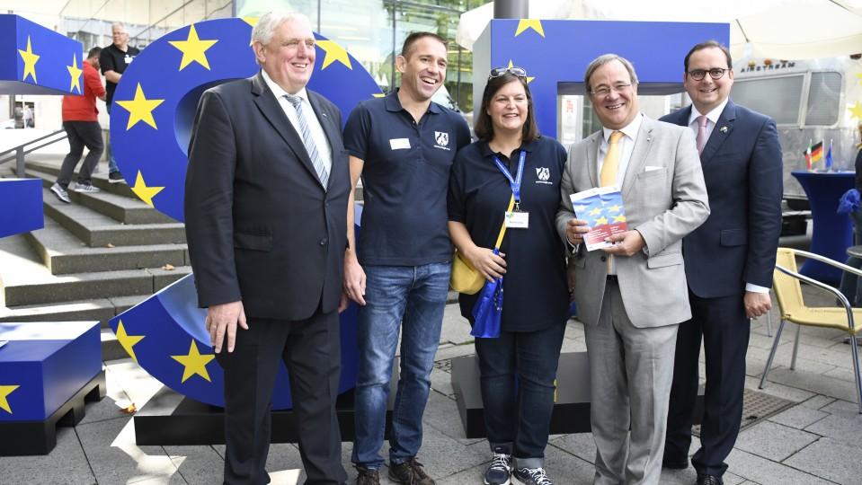 ESF-Stand Minister Laumann (li) und Ministerpräsident Laschet (2.v.r.) vor blauen Großbuchstaben ESF mit gelben Sternchen