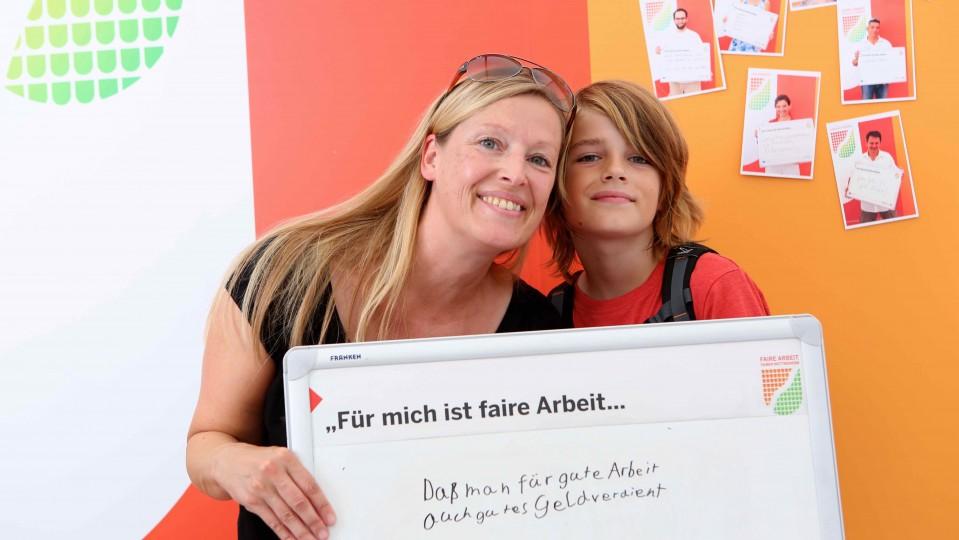 """Fotaktion - Mutter und Sohn halten Tafel mit Satz """"Für mich ist faire Arbeit ...dass man mit guter Arbeit auch gutes Geld verdient"""""""