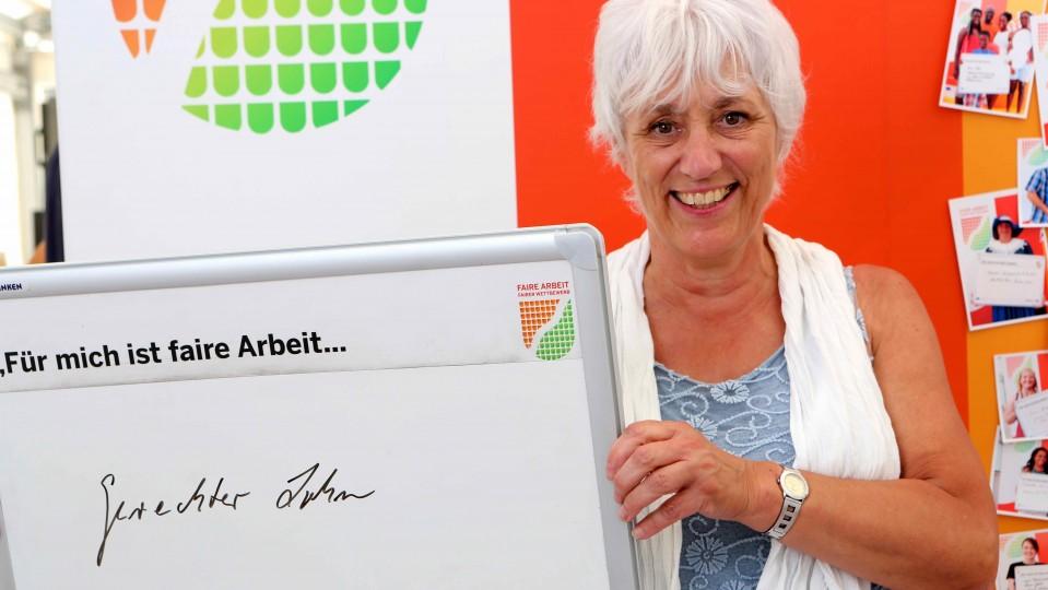 """Fotoaktion - Frau hält Tafel mit dem Satz """"Für mich ist faire Arbeit ...gerechter Lohn"""""""