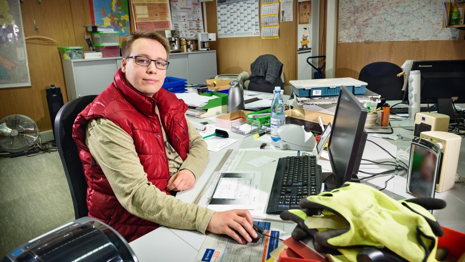 Junger Mann in einem Büro arbeitet am PC