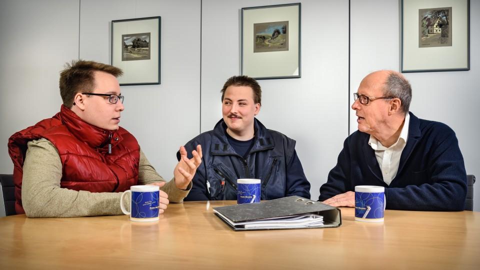 3 Männer sitzen an einem Tisch und reden