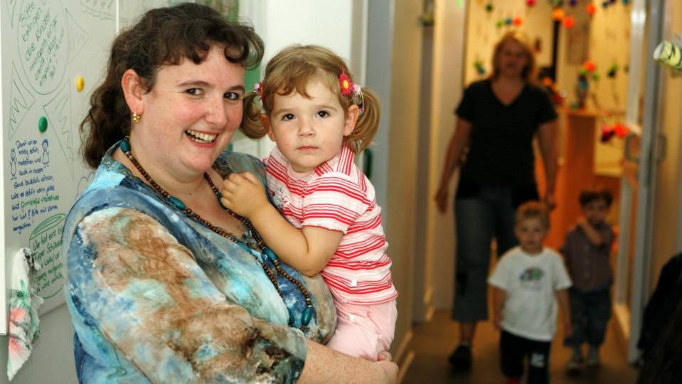 Frau mit Kind auf dem Arm - im Hintegrund Blick in Kita