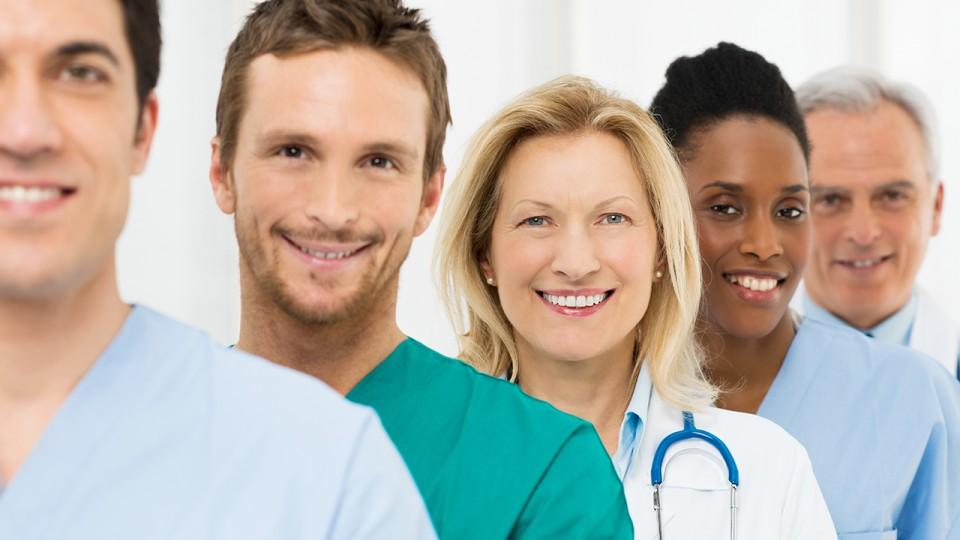Gruppe glücklicher erfolgreicher Ärzte steht im Krankenhaus in einer Reihe