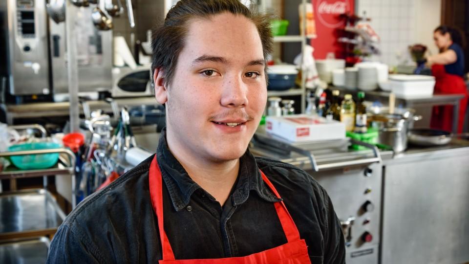 Junger Mann im Porträt mit roter Schürze, im Hintergrund Küche eines Restaurantbetriebs