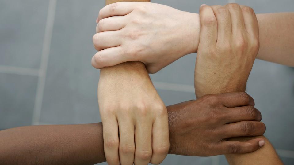 Vier Hände formen ein Viereck als Symbolbild für gegenseitige Hilfe