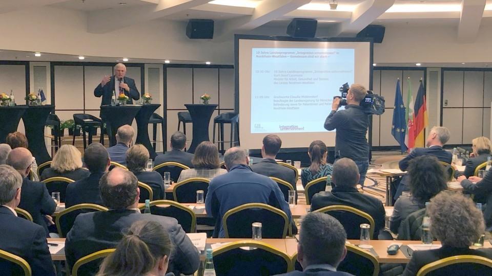 """Minister Laumann an einem Rednerpult vor Publikum bei der Veranstaltung """"10 Jahre Landesprogramm Integration unternehmen!"""""""