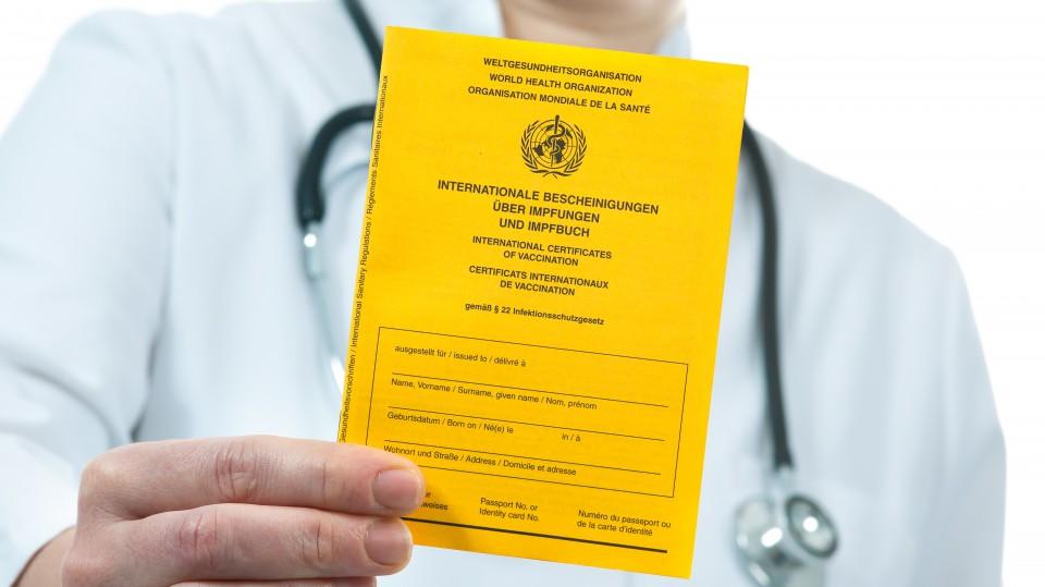 Arzt hält einen gelben Impfpass in der Hand