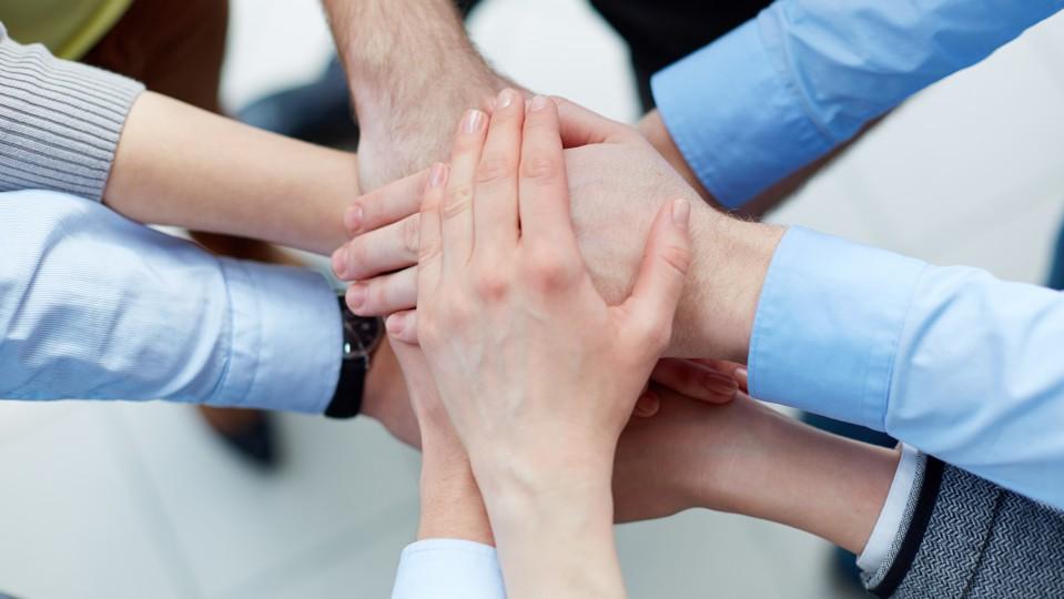 Hände von Geschäftsleuten liegen aufeinander