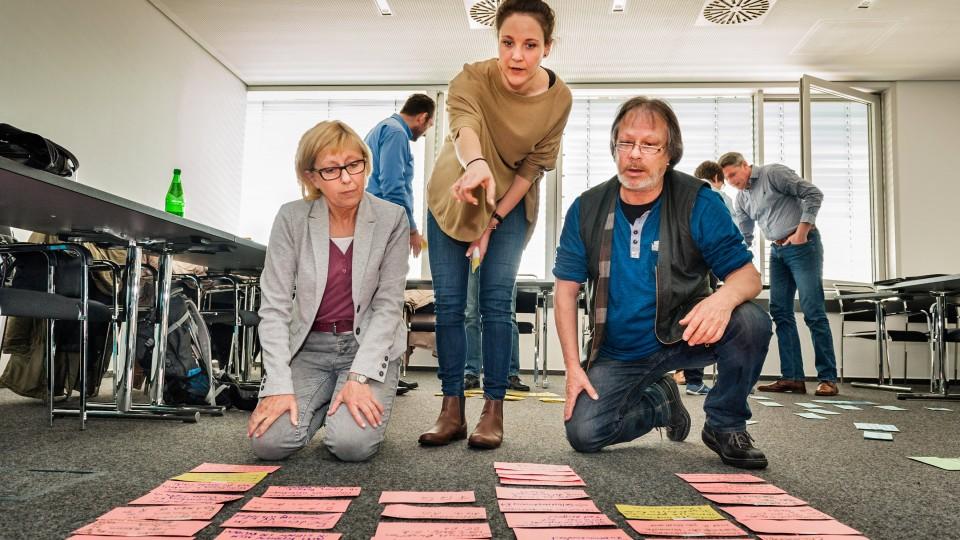 Foto: Zwei Frauen und ein Mann beugen sich über die Karteikarten, die auf dem Boden ausgelegt sind